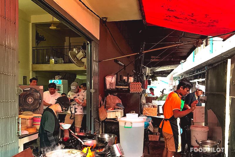 Jay Fai steht am Wok, Gaeste schauen zu und fotografieren